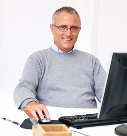 An older man is dressed casually and sitting down at a computer. He is looking at the new Scribendi.com 2.0 website.