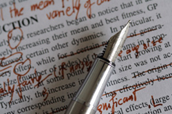 A close-up of a written assignment. The assignment has been marked in red pen by a professional editor; the pen is resting on top of the assignment.