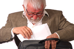 A male professor is placing a grant proposal into his briefcase.