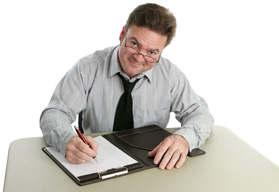 A male professor is sitting at a desk with a clipboard in front of him. He is poised for writing and is beginning the first steps of grant writing.