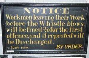 "A sign reading ""Workmen leaving their Work before the Whistle Blows, will be fined 2/6 for the first offence, and if repeated will be Discharged."" There are a number of unnecessary words capitalized."