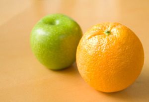 A photo of an apple and an orange on a table.