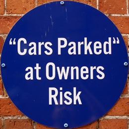 "A large blue sign that reads """"Cars Parked"" at Owners Risk;"" this shows the incorrect usage of double and single quotation marks."