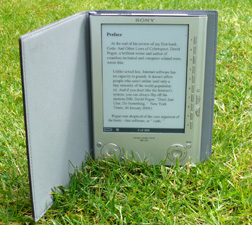A photograph of a Sony eBook Reader resting in the grass. This shows the overall versatility of e-books and the value of e-book publishing.