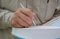 A close-up of a male author signing an autograph on the inside cover of the novel he hopes to get published.