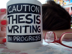 "In the background, a girl is sitting with her head down on a desk. She is wondering, ""What is a thesis?"" The foreground contains a pair of glasses and a large coffee mug with ""Caution, thesis writing in progress"" printed across the front."