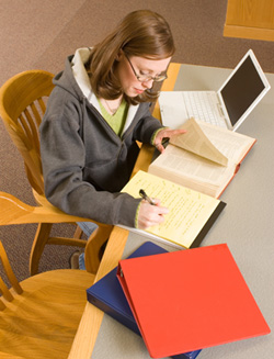 A female student is sitting at a desk in a library; she is taking notes from a large book. There are two binders on the table, along with a laptop computer. She is in the process of thesis editing.