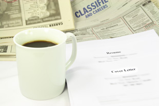 A photo with a cup of coffee, a resume, and the newspaper open to the classified section.