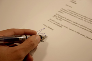 A close-up of a hand signing a query letter with a ballpoint pen.