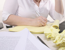 A close-up of a female student at a desk; she is writing on a pad of paper. The desk is covered in balls of crushed up paper. She is trying to improve her writing skills.