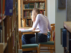 A female student is sitting at a table in a library working on her MLA formatting and MLA style.