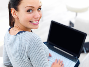 A student smiles while working on her computer. She is writing an essay in the active voice.