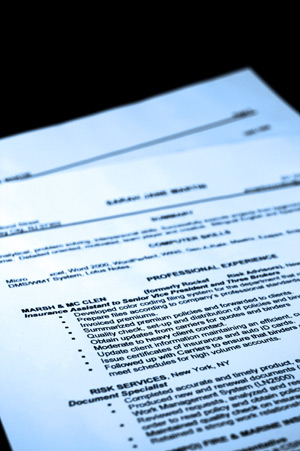 A piece of paper is sitting on a black backdrop. The paper is showing proper resume format.