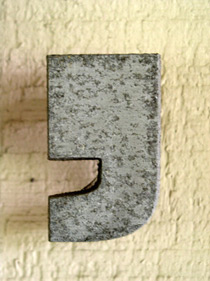 A comma key from a movable type machine is pictured.