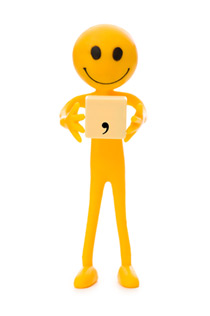 A bendable yellow man with a large smile is holding a wooden sign with a comma on it.