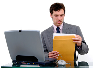 An employer is sitting at a desk with a laptop in front of him. He is holding a manila envelope and reviewing a nicely formatted cover letter.
