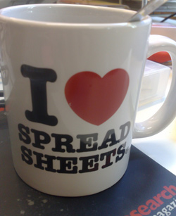 "A coffee mug is sitting on a table. Written on the mug is the saying ""I Love Spread Sheets"" where ""love"" is written as a heart. This shows how much the person using the mug loves track changes in Excel."