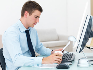 A young man is sitting in front of a desktop computer, drinking a coffee and writing a cover letter.