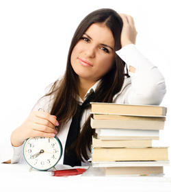 A flustered female student is sitting at a desk with a pile of books in front of her. She is clutching her head in one hand and holding a clock in the other.