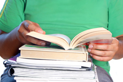 A student is sitting in front of a white background. There is a pile of books on the student's lap; he is reading the top book, which outlines how to write a book report.