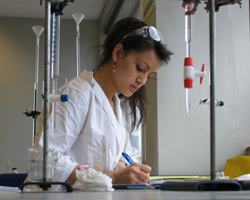 A female student is standing in a laboratory. She has safety goggles propped on her head and is writing observations in a lab report or scientific paper.