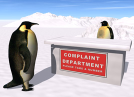 "A penguin is sitting behind a desk. There is a sign on the desk that reads ""Complaint Department: Please take a number."" Another penguin is standing in front of the desk with a letter of complaint waiting to be served."