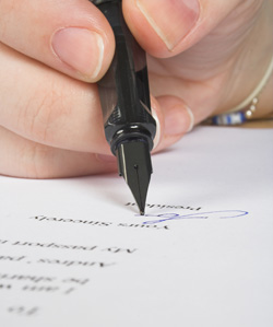 A woman is signing her name at the bottom of a recommendation letter.