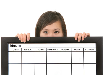 A woman is holding a large editorial calendar. The calendar covers the bottom half of her face and most of her body.