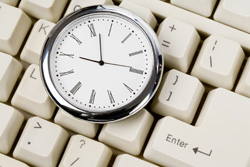 A pocket watch sits on top of a keyboard. This shows the importance of time management skills in finding time to write.