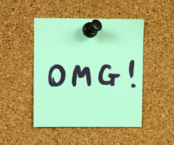 "A sticky note is pinned to a corkboard. Written on the note is the acronym ""OMG""."