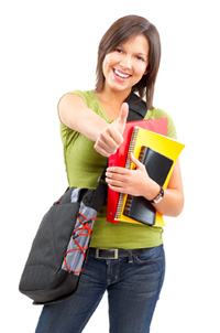 A college student is holding a stack of books, including research for her college admissions essay, in her left hand. She is giving the thumbs-up with her right hand.