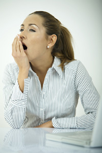 A woman is sitting at her desk. Her hand is in front of her mouth and she is stifling a yawn because she cannot stay awake.