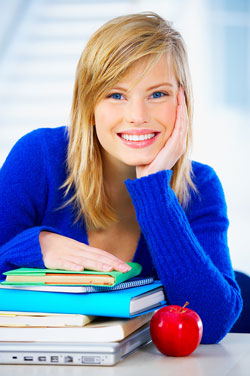 An attractive young woman wearing a bright blue sweater sits behind, and rests her hands on, a stack of books containing information on APA style formatting.