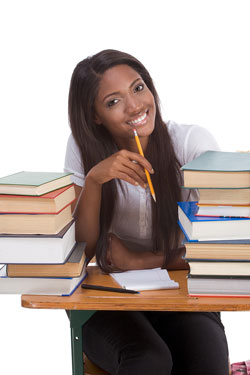A young, attractive female student sits at a desk with books stacked on the desk to either side of her, a pencil in her hand, and a notepad on the desk in front of her. She is trying to add the books to her APA Reference Page.