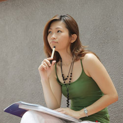 A female student wearing a green tank top is sitting outside, with a notebook on her lap, contemplating how to write an APA title page.