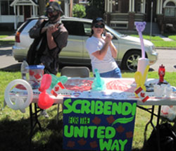 "A clown and a young woman pose behind a table that has balloon animals and a sign on it said says, ""Scribendi for the United Way."""