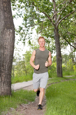 A young man dashes down a path surrounded by trees.