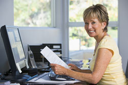 A woman is on the computer in her home office. She is smiling as she reads an example recommendation letter.