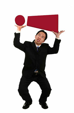 An Asian man in a business suit carrying a large exclamation mark.