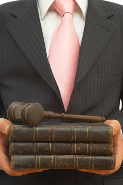 The torso of a man in a black suit with a pink tie, holding three leather books with a gavel sitting on top of them.