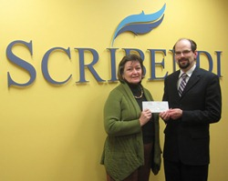 Female representative from Mary Webb Cultural and Community Centre accepting a check from the Vice-President of Scribendi.com.