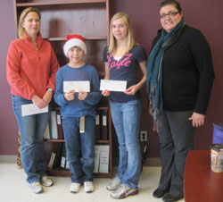Two adults and two children stand with cheques donated by Scribendi.com to the McFadden fundraiser.
