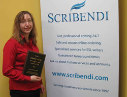 Scribendi.com President, Chandra Clarke, is standing next to a Scribendi.com sign holding an OWIT award plaque.