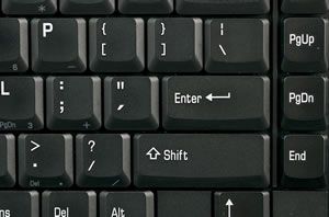 A black keyboard with white letters; particular attention is paid to the punction mark keys.