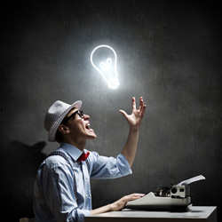 An author screenwriting on his type writer has a bright light bulb over his head.