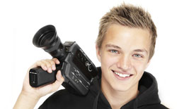 A young man holds a camera and looks straight ahead; he is participating in Script Frenzy.