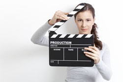 A young brunette woman holding a film clapper; she hopes that her hard work in the screenwriting process will land her a movie deal.
