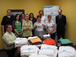 Scribendi.com staff stand with the clothing they collected in their shirt drive.