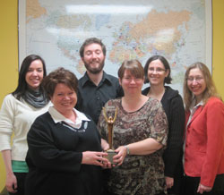 The Scribendi.com staff stand in front of a large map of the world while holding their International Stevie Award for Best Writing/Content.