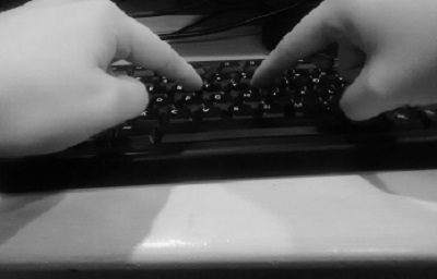 Two fingers are poised over a computer keyboard.